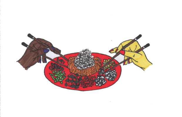 Red platter with piles of sliced vegetables and fish, two hands on either side, one yellow, one brown, holding chopsticks