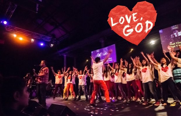 Dancers on darkly lit stage, wearing white t shirts, band playing in image left including man holding guitar, red loveheart above stage inscribed with 'LOVE GOD' in capitals