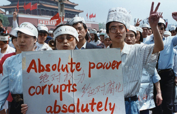 Protestors at Tiananmen Square, three men wearing paper hats saying 'China Times' and holding banner saying Absolute power corrupts absolutely'