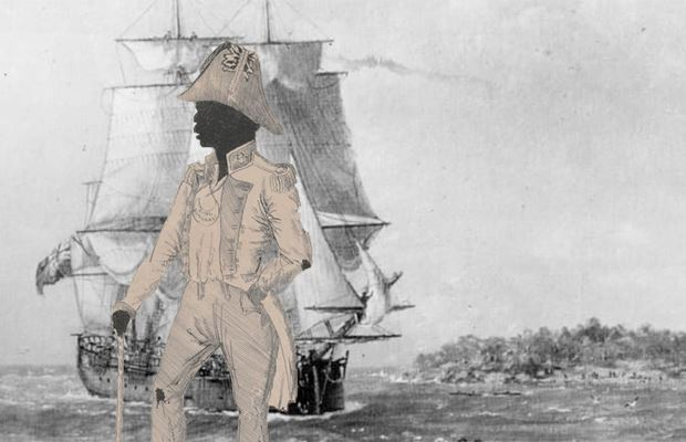 Bungaree, dressed in colonial clothes, stands in front of the Endeavour ship.