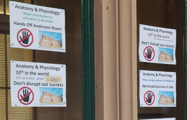 "Photo of windows of Anderson Stuart building covered with posters which read ""Hands off Anderson Stuart"""
