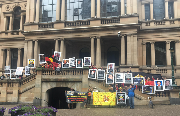 Protestors stand along the Sydney Town Hall steps, with images of deceased Indigenous people's faces.