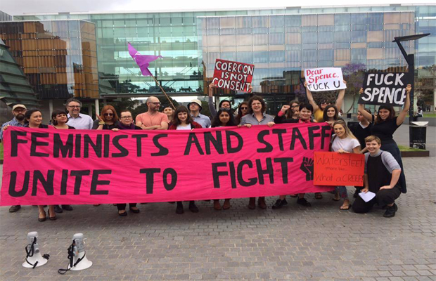 "An image of a protest organised by the Women's Collective. Protestors bear a sign that reads ""feminists and staff unite to fight"""