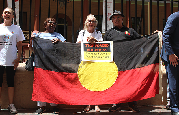 Hazel Collins, Aunty Doreen Webster, and Michael Welsh, speakers at the 2019 Sorry Day rally holding Aboriginal Flag outside NSW State Parliament
