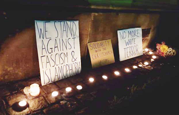 "An image of the vigil on Monday night, with candles and placards reading ""we stand against fascism Islamophobia,"" ""Solidarity with the Christchurch victims"" and ""No more white terror,"" surrounded by a series of candles."""
