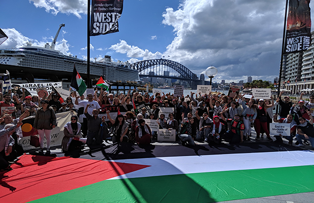 Image of protestors gathered with large Palestinian Flag in front of Sydney Harbour Bridge