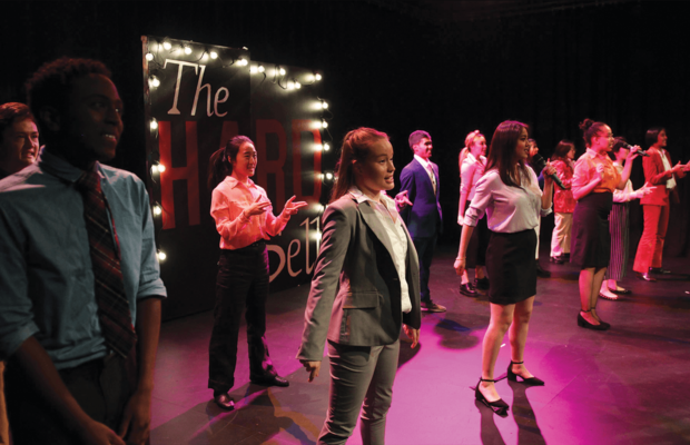 The PoC Revue V cast stands on a pink-lit stage and sings.