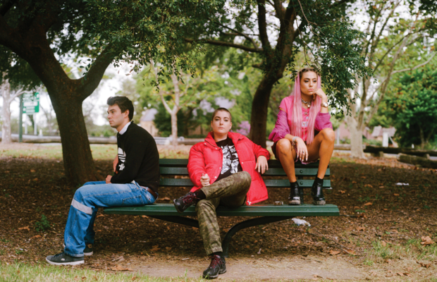 Three people sit on a park bench looking unhappy.