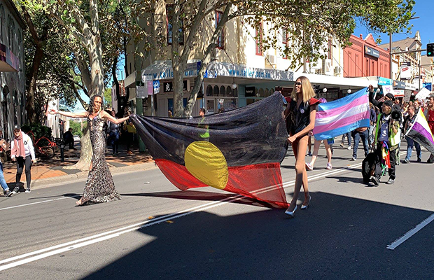 Two people walking along King street leading the rally holding an Aboriginal flag, followed by a Transgender Pride Flag