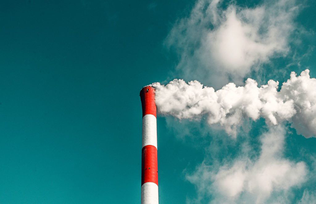 Image of a smoke stack emitting pollution, foregrounding a blue sky with clouds.