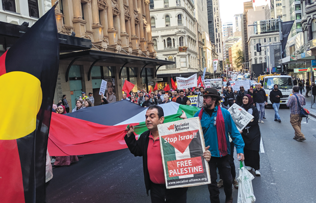"A man holding a Socialist Alliance paper with text ""Stop Israel Free Palestine"". Behind is a Palestinian flag being carried by many, and to the left is an Aboriginal flag."