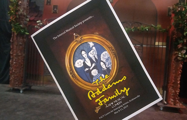 An image of the poster for the show, featuring an illustration of the Addams Family