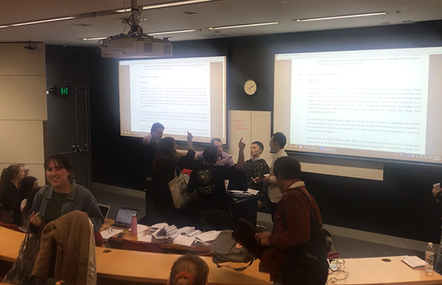 A photo of a heated debate between multiple people at the SRC meeting in a New Law seminar room