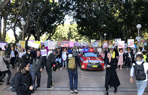 Photograph: the front of the march walking through Hyde Park, people holding pro-choice posters, and among the crowd is a police car. In front of the crowd are other journalists photographing the march.