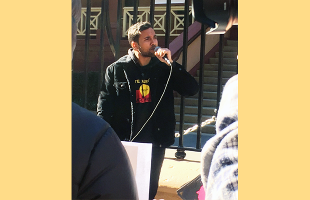 Gavin Walker speaking at the rally with a microphone in hand.
