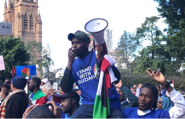A photo of a protester hoisted on the shoulders of two others, holding a Sudanese flag and speaking into a megaphone