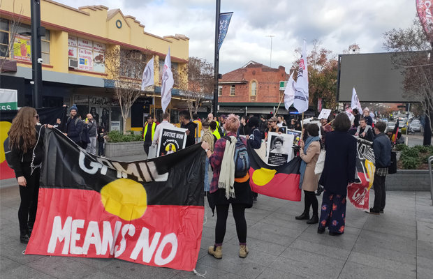"Photo: Protesters stand in Liverpool. A large Aboriginal flag is pictured, with white text that reads ""GAMIL MEANS NO."" There is a second Aboriginal flag, and other posters that read ""JUSTICE NOW""."