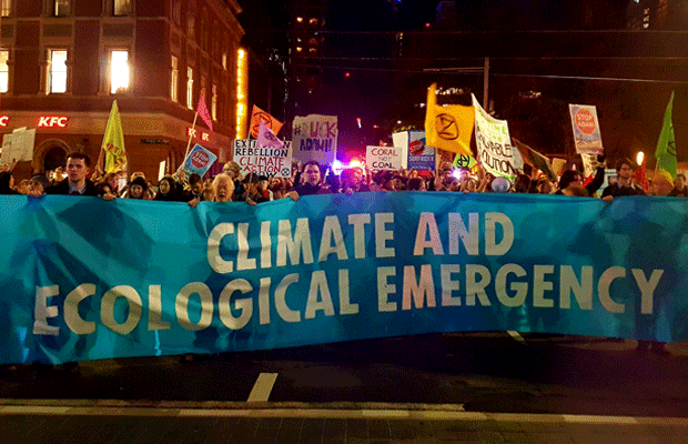 "Protesters on George St hold up signs and a blue banner saying ""climate and ecological emergency."""