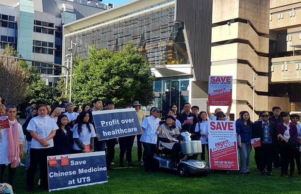 students and staff on UTS alumni green hold placards which read healthcare over profit