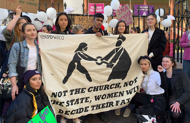 "Photo of the University of Sydney Women's Collective, holding a banner which reads ""Not the church, not the state, women will decide their fate"", in front of NSW parliament house."