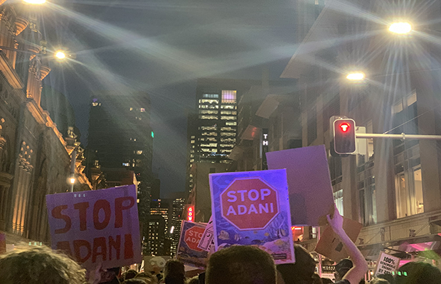 Photo from the climate strike along George Street, picturing signs that read STOP ADANI.