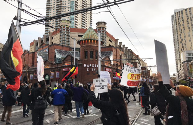 "Protesters march through Market City intersection. Several Aboriginal flags are in the photo, which is taken from the midst of the crowd. In the middle is a sign that reads ""You are on Aboriginal Land."""
