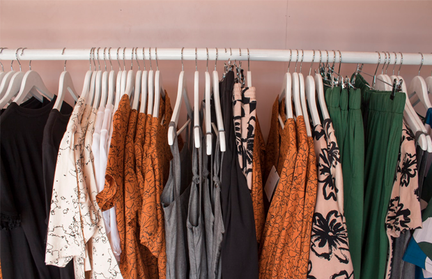 A photo of a coatrack filled with a random assortment of clothing on coathangers.