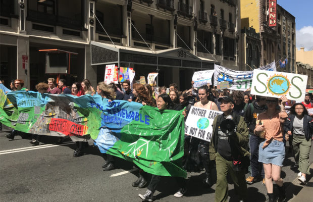 A group of people protesting and holding a large green and blue banner.
